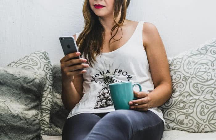 Frau mit iPhone auf Couch